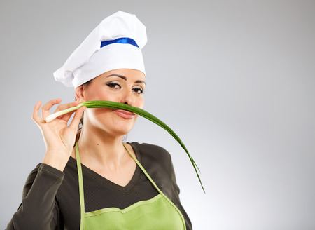 cook out: Woman cook making a moustache out of spring onion Stock Photo