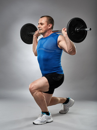 lunges: Man doing lunges with barbell on back in the studio