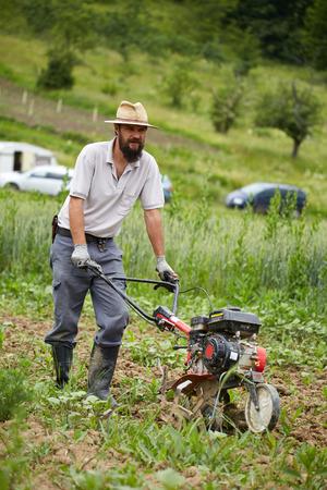 motorised: agricultor joven deshierbe en un campo de maíz con una caña de timón motorizado Foto de archivo