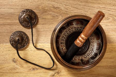 singing bells: Closeup of an ancient tibetan bowl on wood