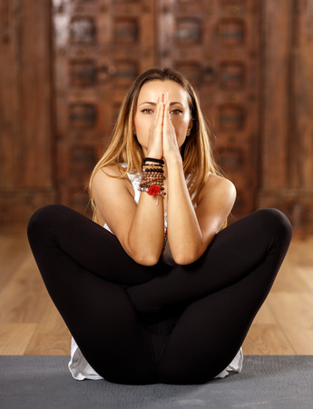 namaskar: Woman yoga trainer in padmasana (lotus) combined with namaskar mudra pose