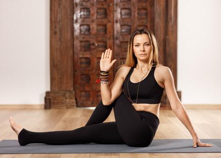 ardha: Woman yoga trainer in ardha matsyendrasana (half seated twist) pose