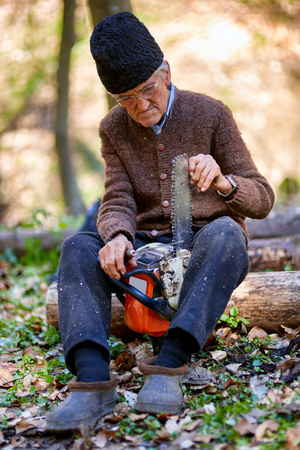 woodcutter: Old woodcutter doing maintenance work to his chainsaw