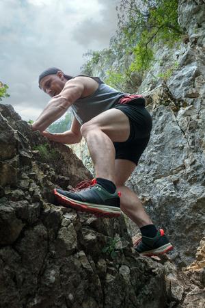 free climbing: Man free climbing on rocky face of a mountain