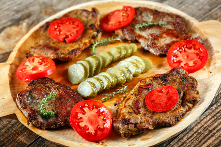 Spiced pork chops barbecue on a wooden board with tomatoes and pickles