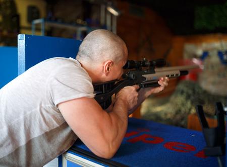 hombre disparando: Hombre joven que tira un rifle en un parque de atracciones Foto de archivo