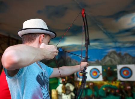 Young man shooting a bow at an amusement park Stock Photo - 63353011