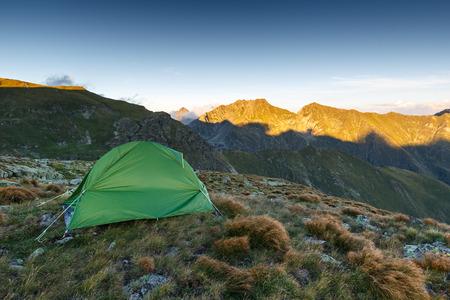 Tent on the mountain summit at sunset in Romanian Carpathians