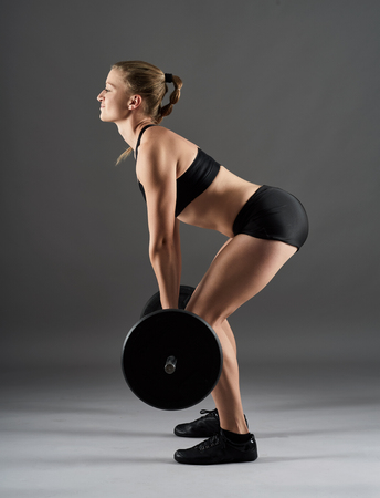 sexy woman standing: Young fit woman with heavy barbell doing deadlift for back workout