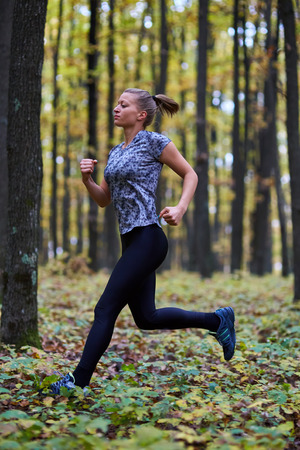 Young woman trail running through forest in the autumn Stock Photo