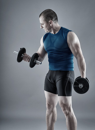 Fitness man doing biceps curl with dumbbells on gray background