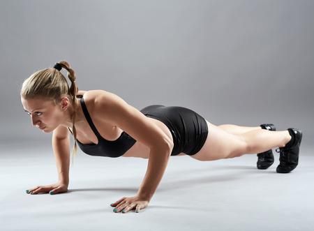 Athletic young woman doing pushups on gray background