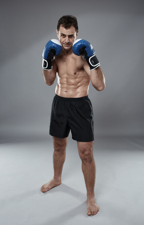 Kickbox fighter in guard stance full length on gray background
