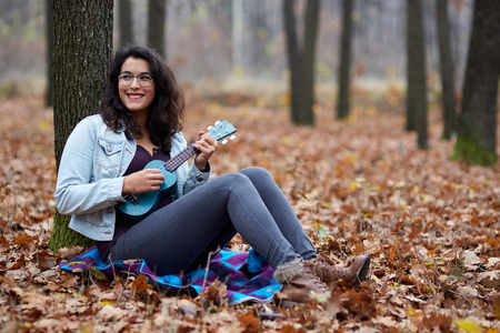 Hispanic young girl playing ukulele outdoor in the forest