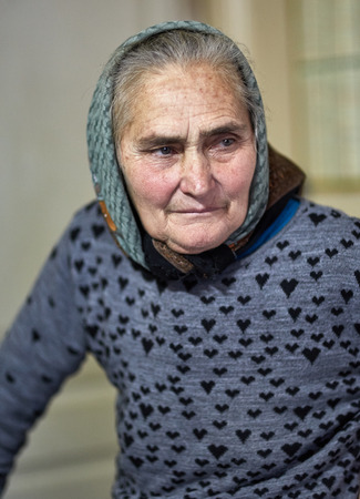 Portrait of an old farmer woman indoor in her home photo