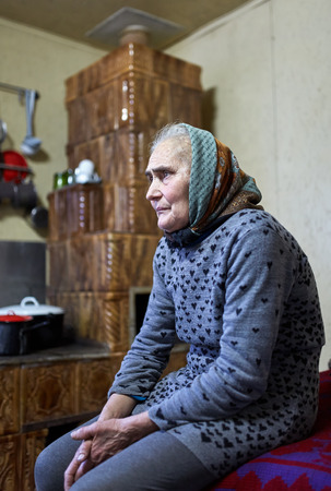 Senior peasant farmer woman sitting in her home photo