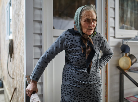 Old farmer woman outdoor near her house photo