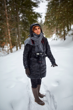 snowdrifts: Tourist woman with camera hiking on a snowy trail in the mountains