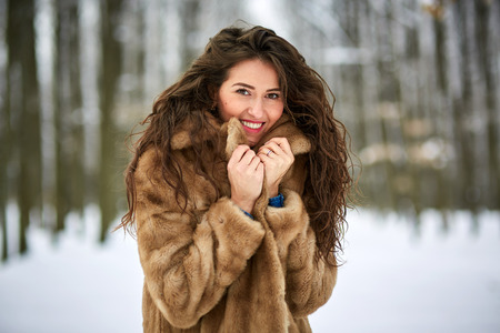 Young woman having fun outdoor in the snow, closeup with selective focus