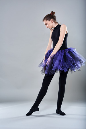 Young ballerina in various postures on gray background
