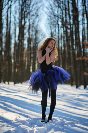 choreographic: Ballerina dancing outdoor in the snow, in a forest