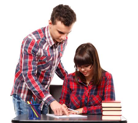Teenage boy helping his girlfriend with homework Stock Photo