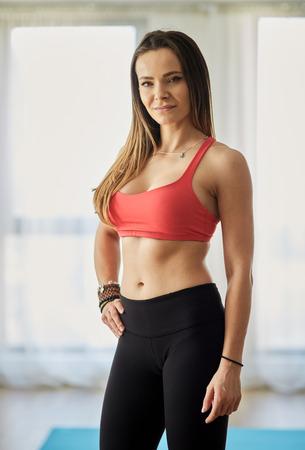 Attractive fitness model in bra and yoga pants posing indoor