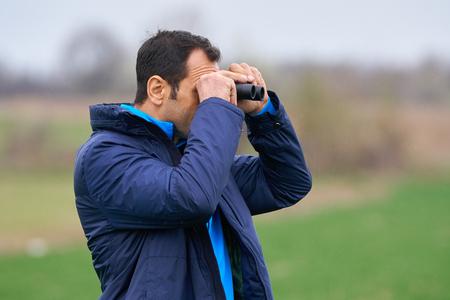 to observer: Closeup of a man watching birds through binoculars