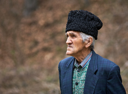 Old farmer closeup portrait outdoor in the forest photo