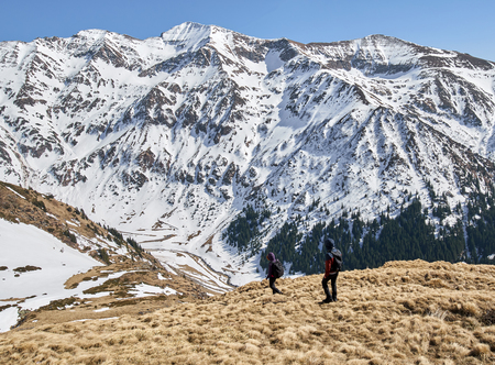 Family hiking into the rocky mountains at springtime photo