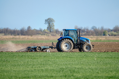 harrowing: Tractor harrowing ploughed land in a spring day