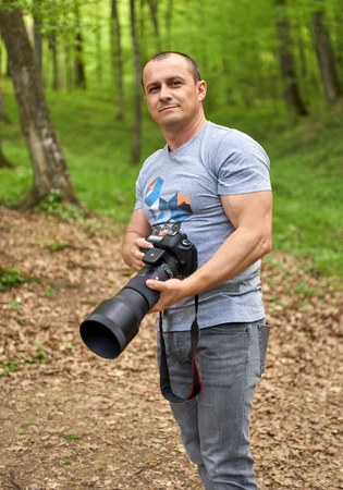 Caucasian professional photographer holding a camera with big telephoto lens attached
