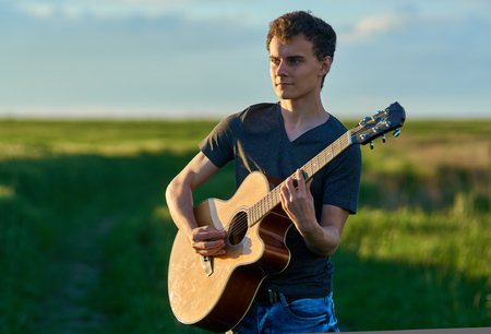 Teenage boy playing guitar at sunset in a wheat field photo