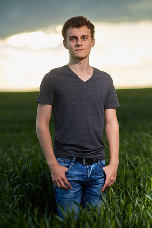 Teenage boy standing in a wheat field at sunset, closeup portrait photo