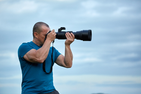 Wildlife photographer with a big telephoto lens on camera