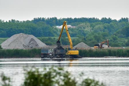 Excavatrice chargant du sable et du pavé dans un camion sur un lac Banque d'images