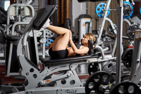 Young woman working her quads at machine leg press
