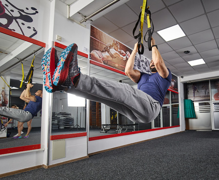 Fit man working with suspension straps in the gym