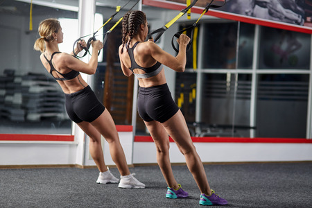 Two fitness girls working out with suspension straps in a gym