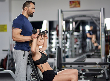 Personal instructor assisting young woman with shoulder workout