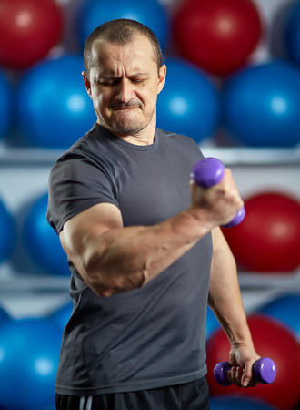 Funny image of a big strong man with very small dumbbells Banque d'images