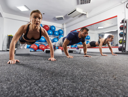 Fitness instructor and women doing pushups in the gym