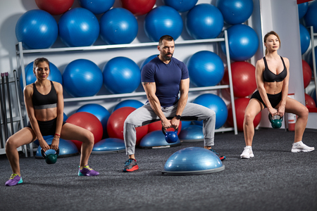 Fitness instructor with two girls working out with kettlebell Banque d'images