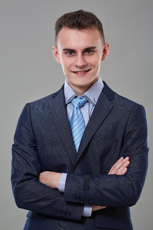 Young man in classic business suit with arms folded