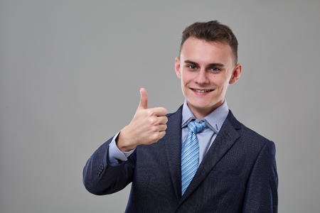 Young man in classic business suit, showing thumbs up sign Banque d'images