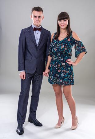 Happy teenage couple in full length studio shot