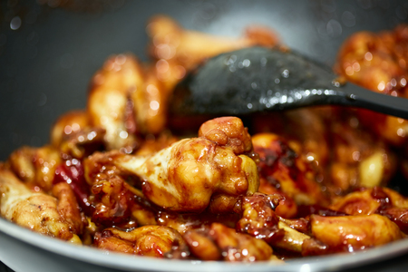 Asian recipe of caramelized chicken wings cooking in the pan Banque d'images