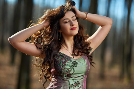 Closeup portrait of a beautiful young brunette in green dress outdoor Banque d'images