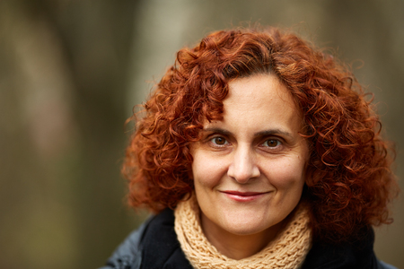 Closeup of a curly red haired middle aged woman outdoor