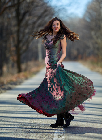 Woman in dress dancing in the middle of the road